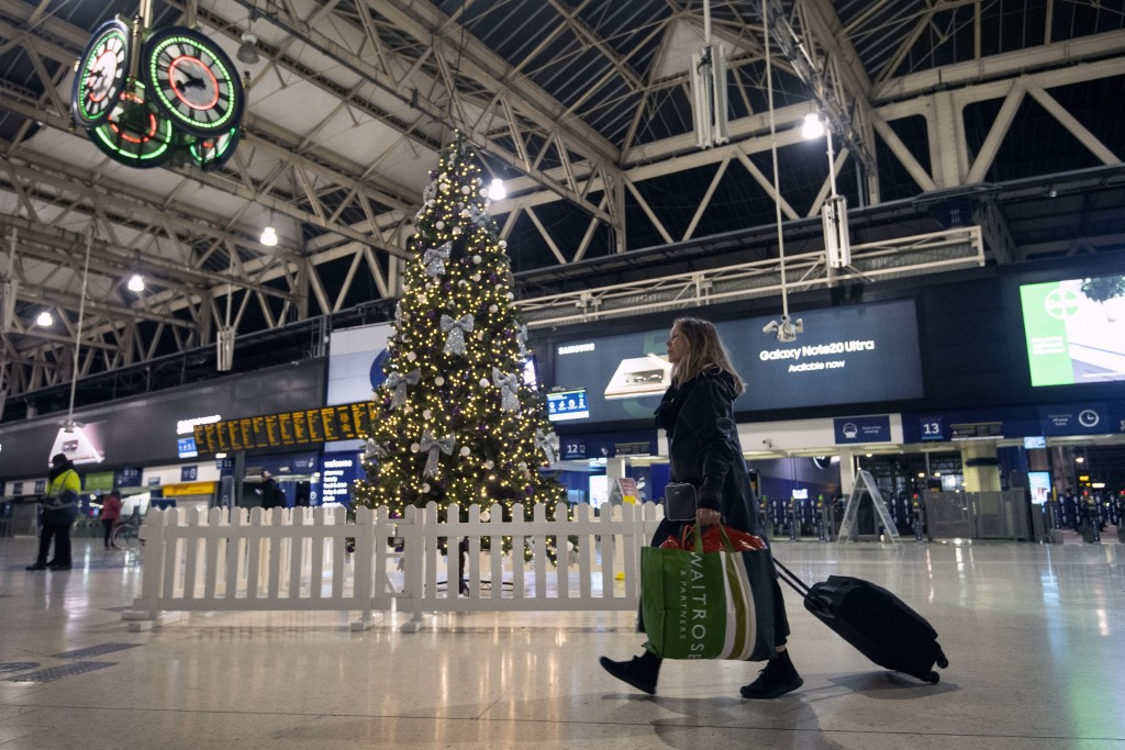 FILE - In this Sunday Dec. 20, 2020 file photo a woman pulls a suitcase past the Christmas tree on the concourse of Waterloo Station in central London...