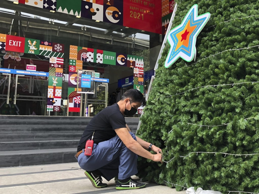 A worker wearing a face mask to help prevent the spread of coronavirus prepares an artificial Christmas tree outside a shopping mall that would normal...
