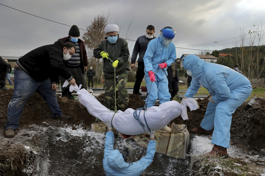 Volunteers and relatives wearing protective clothing and masks lower the body of Ghorbanali Mahmoudi, 59, who died from COVID-19 into a grave at a cem...