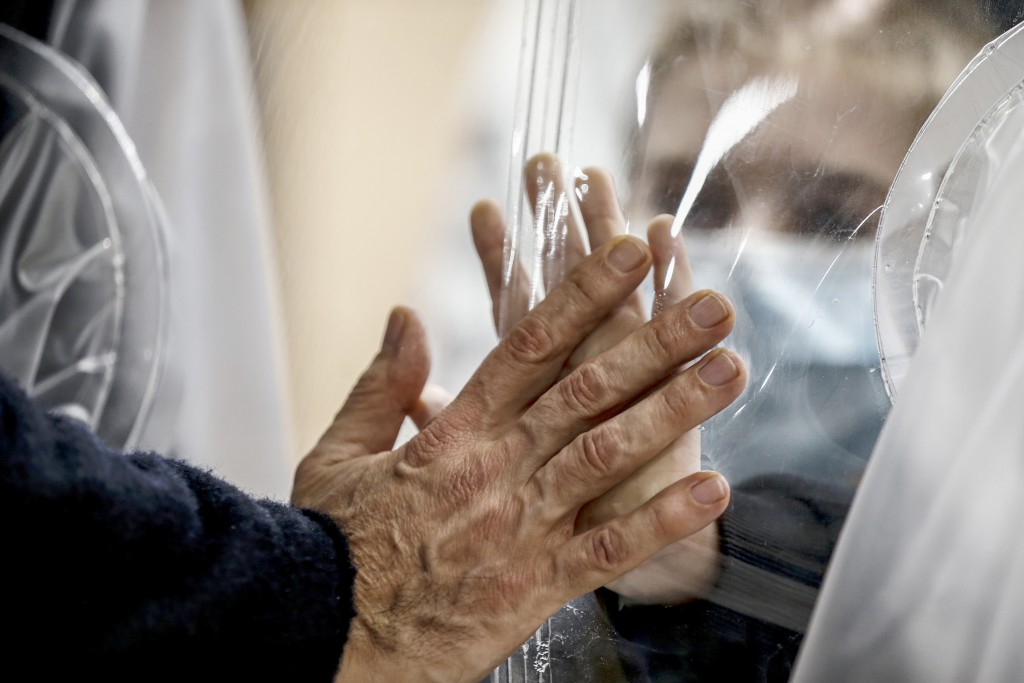FILE - In this Dec. 22, 2020, file photo, relatives touch each other's hand through a plastic film screen and a glass to avoid contracting COVID-19 at...