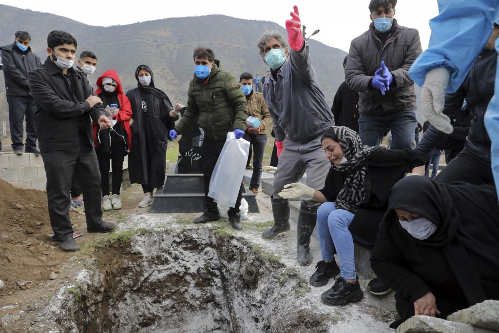 Relatives of Keyumars Ziaee, 60, who died from COVID-19 mourn over his grave at a cemetery in the Shir Kola village on the outskirts of the city of Gh...