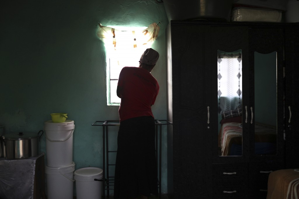 Matefo Litali opens the curtains of her small rented room that she shares with her youngest daughter and a granddaughter, in the town of Ha Thetsane, ...