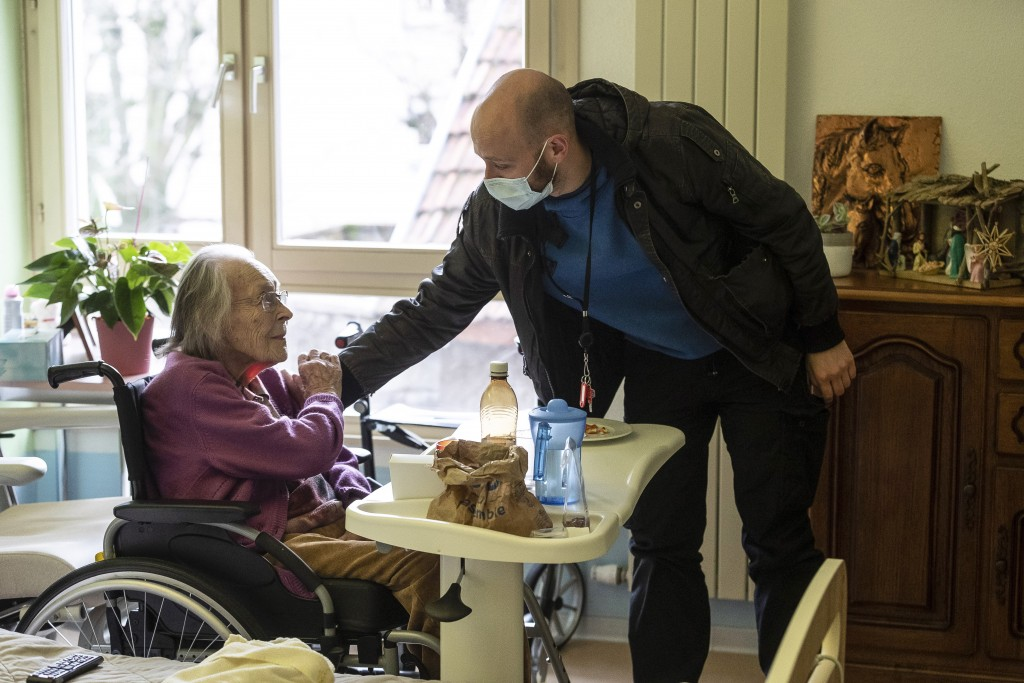 Marguerite Mouille, left, is greeted by her grandson Thierry Mouille at a nursing home in Kaysesberg, eastern France, Monday Dec. 21, 2020. Thierry Mo...