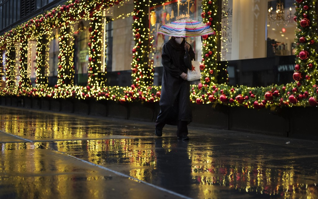 FILE - In this Nov. 30, 2020, file photo, a shopper walks by holiday window displays in New York. All most people wanted for Christmas after this year...