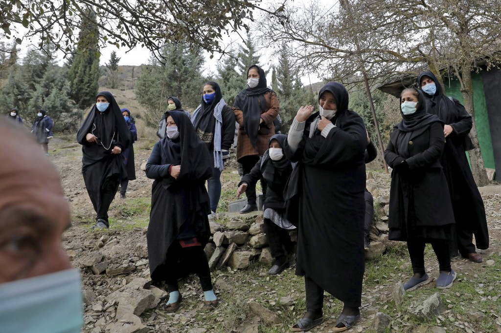 Relatives of Keyumars Ziaee, 60, who died from COVID-19 mourn at a cemetery in the Shir Kola village on the outskirts of the city of Ghaemshahr, in no...