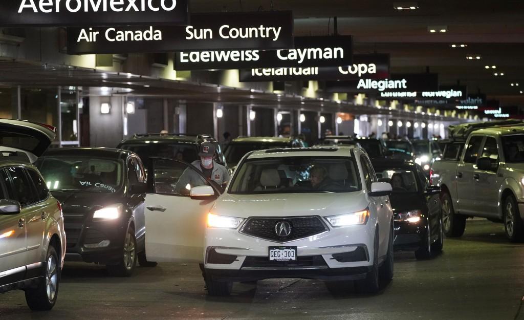 Motorists drop off travellers at Denver International Airport Tuesday, Dec. 22, 2020, in Denver. (AP Photo/David Zalubowski)