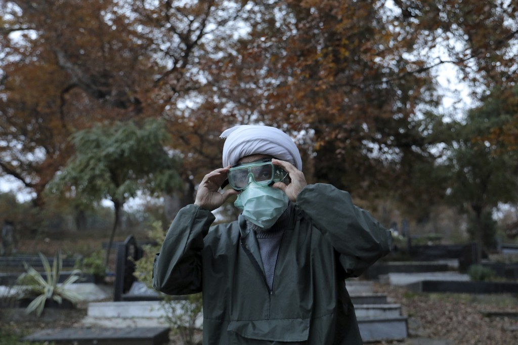 Ali Rahimi, 53, a volunteer cleric wearing protective clothing prepares for a funeral of Rahmatollah Zakeri, 70, who died from COVID-19 at a cemetery ...