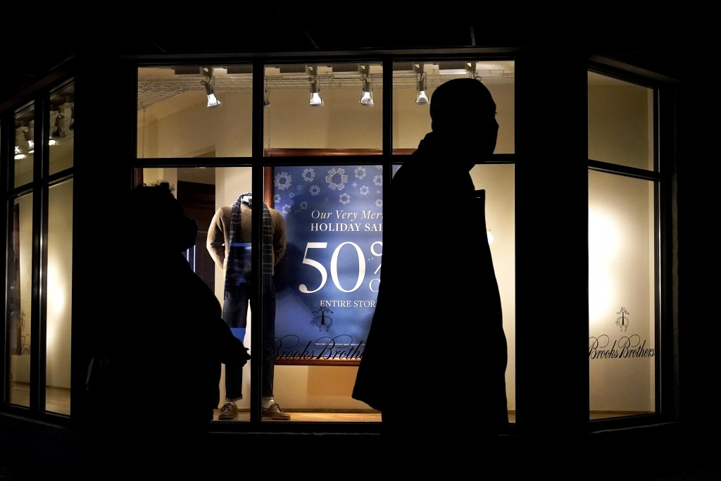 FILE - In this Saturday, Dec. 19, 2020 file photo, people walk past the window display of a store in Skokie, Ill. A closely-watched gauge for U.S. con...
