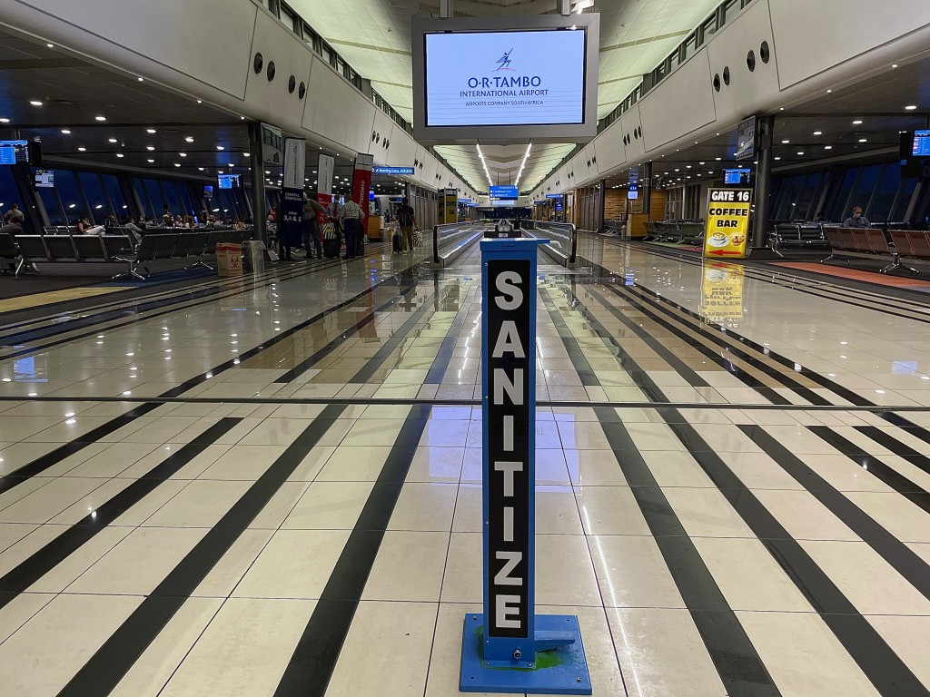 FILE - In this Monday Dec. 21 2020 file photo a hand sanitizing pump stands in the middle of a near empty departure terminal as few passengers board a...