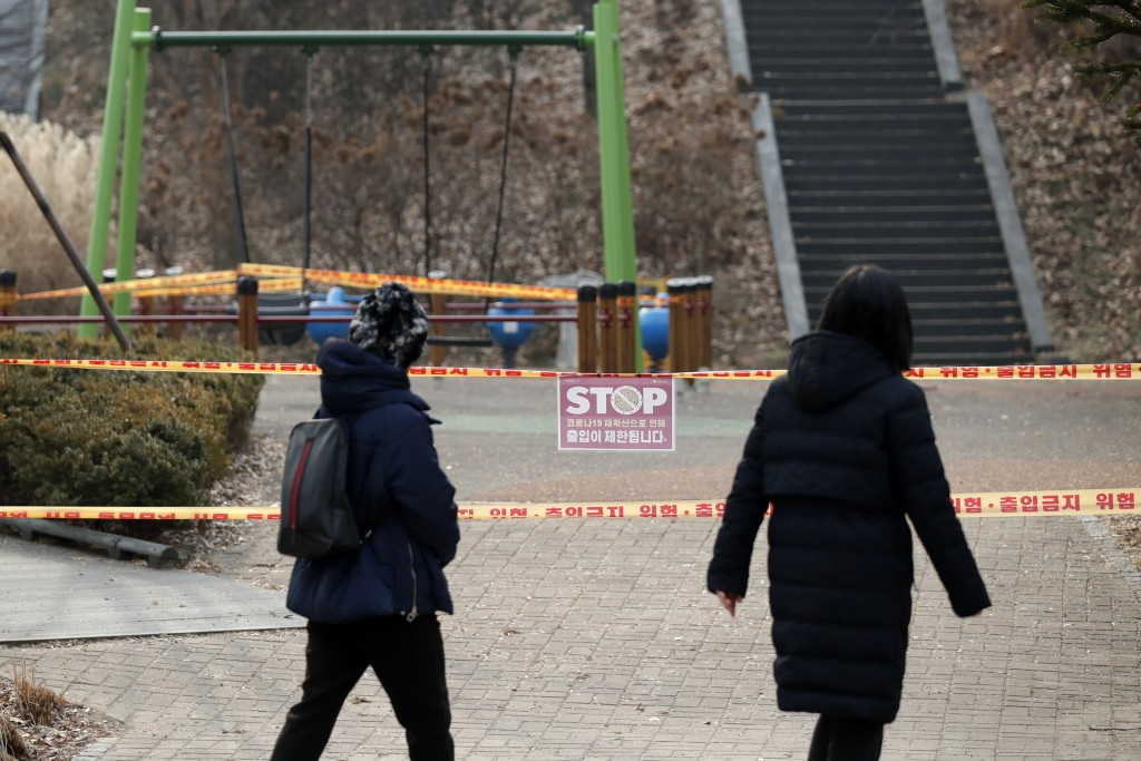 Visitors look at a playground, which is taped off for the social distancing measures and a precaution against the coronavirus at a park in Seoul, Sout...