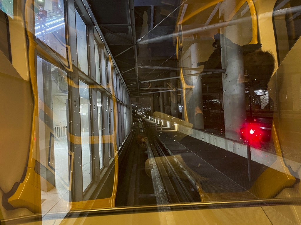 Arriving passengers are reflected in the windshield of the shuttle train linking two terminals at Paris Charles de Gaulle airport Tuesday Dec. 22, 202...