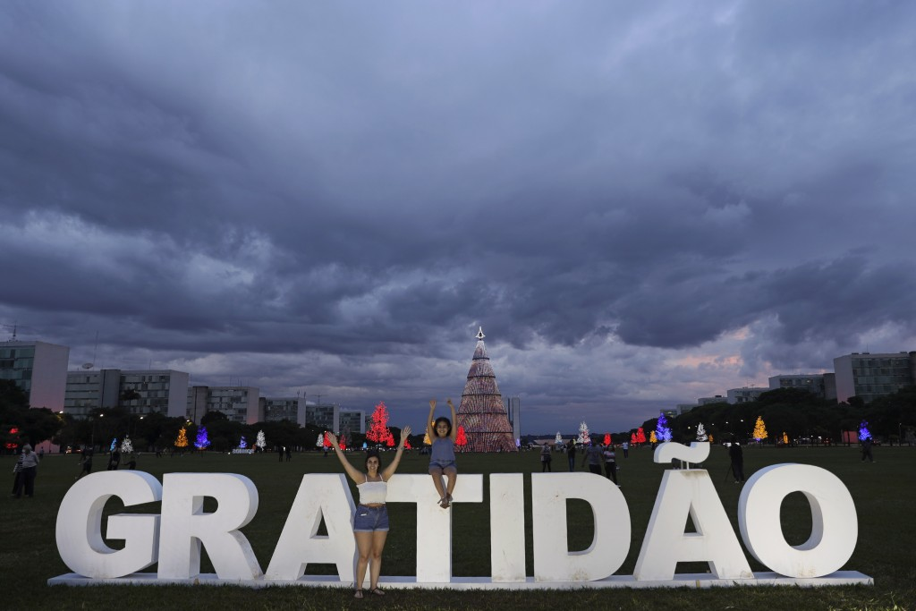 """FILE - In this Monday, Dec. 21, 2020 file photo a mother and daughter pose for photos in front of the Portuguese word """"Gratitude"""" set up at the Esplan..."""