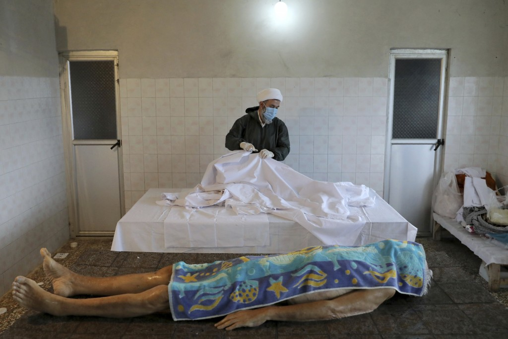 Ali Rahimi, 53, a volunteer cleric wearing protective clothing prepares the body of an 85-year-old man who died from COVID-19 for a funeral at a cemet...