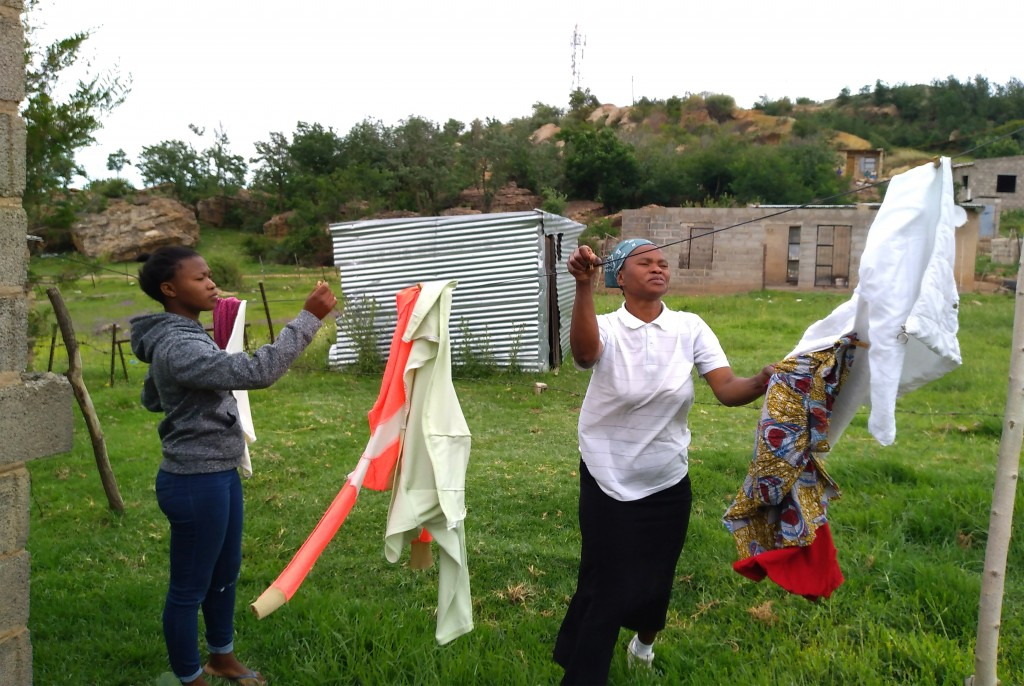 Matefo Litali, 53, hangs laundry with her youngest daughter, Refiloe, 20, whom she regards as her best hope for a better future, in the town of Ha The...