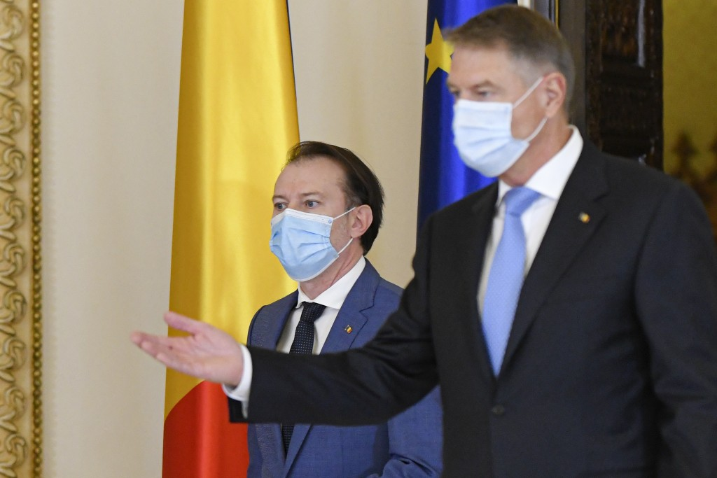 Romanian prime minister-designate Florin Citu, left, walks next to Romanian President Klaus Iohannis shortly before his nomination in Bucharest, Roman...