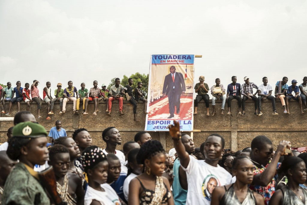 In this photo released by Xinhua News Agency, supporters gather near the poster of Faustin-Archange Touadera, President of the Central African Republi...