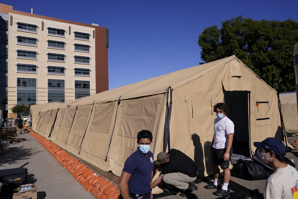 FILE - In this Monday, Dec. 21, 2020 file photo engineers and volunteers stand outside a mobile field hospital at UCI Medical Center, in Orange, Calif...