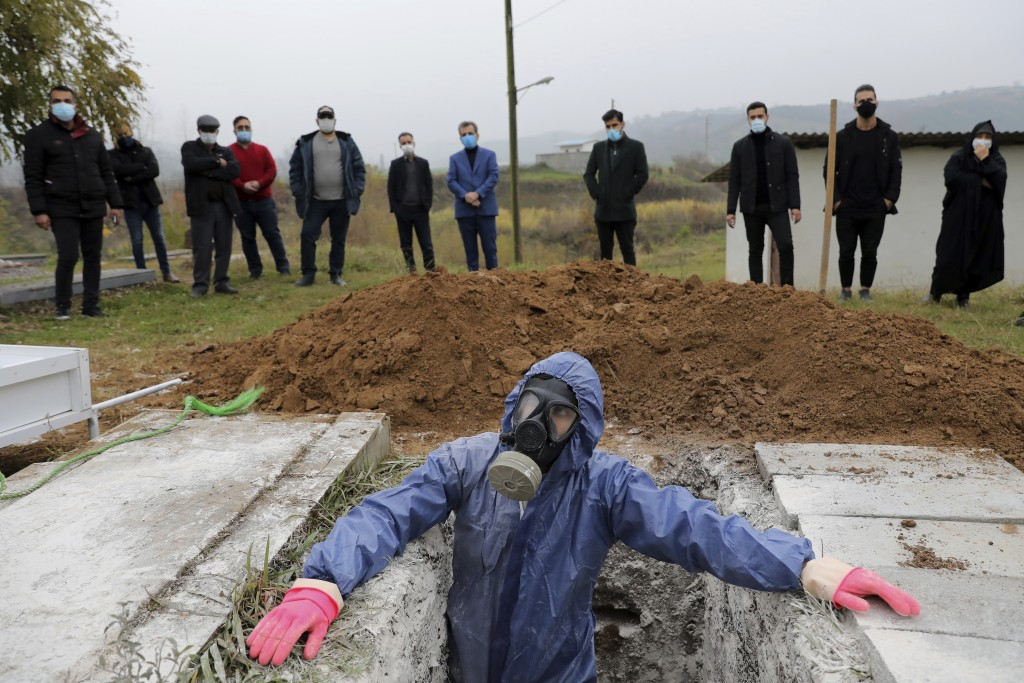 Mohammad Hossein Khoshnazar, 18, a cleric volunteer wearing protective clothing prepares a grave for a funeral of Mahmoud Yousefi, 72, who died from C...