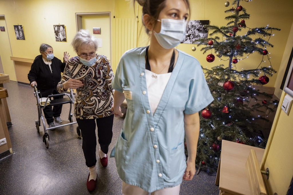 A medical personnel guides residents of a nursing home to the dinning room in Kaysesberg, eastern France, Monday Dec. 21, 2020. France is springing el...