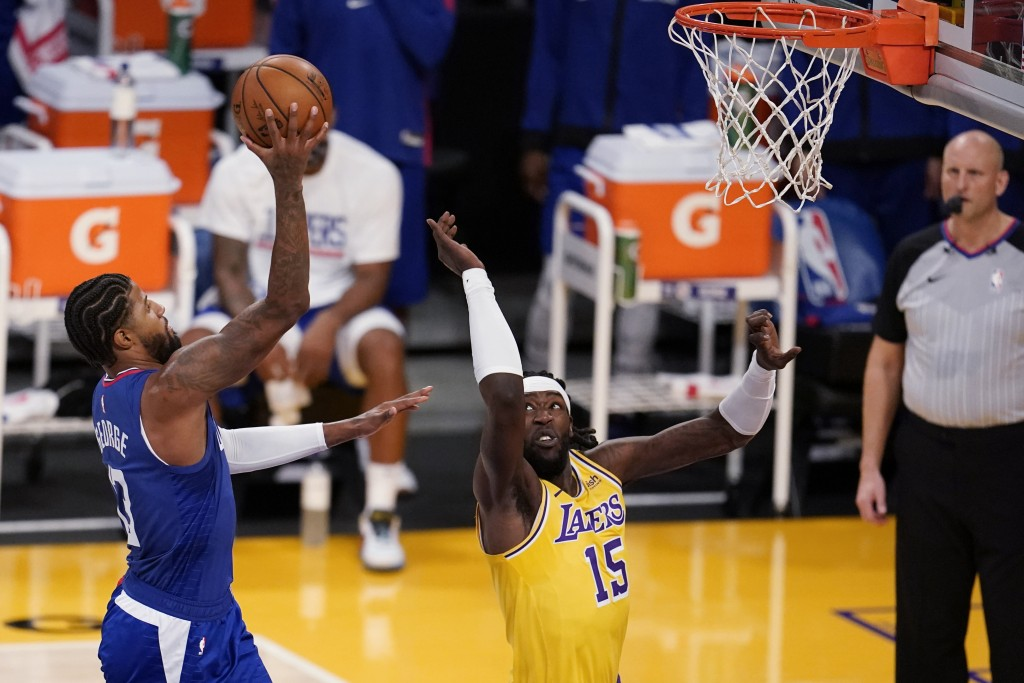 Los Angeles Clippers guard Paul George shoots over Los Angeles Lakers forward Montrezl Harrell during the first half of an NBA basketball game Tuesday...