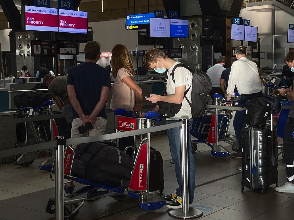 Passengers wait in line to check in for their Air-France flight to Paris at Johannesburg's OR Tambo airport Monday Dec. 21 2020. More and more countri...