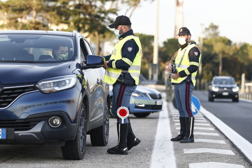 Traffic police speak to drivers at a  checkpoint at the Roma Nord branch toll booth in Rome, Italy, Monday Dec. 21, 2020. Newspapers in Italy have tak...