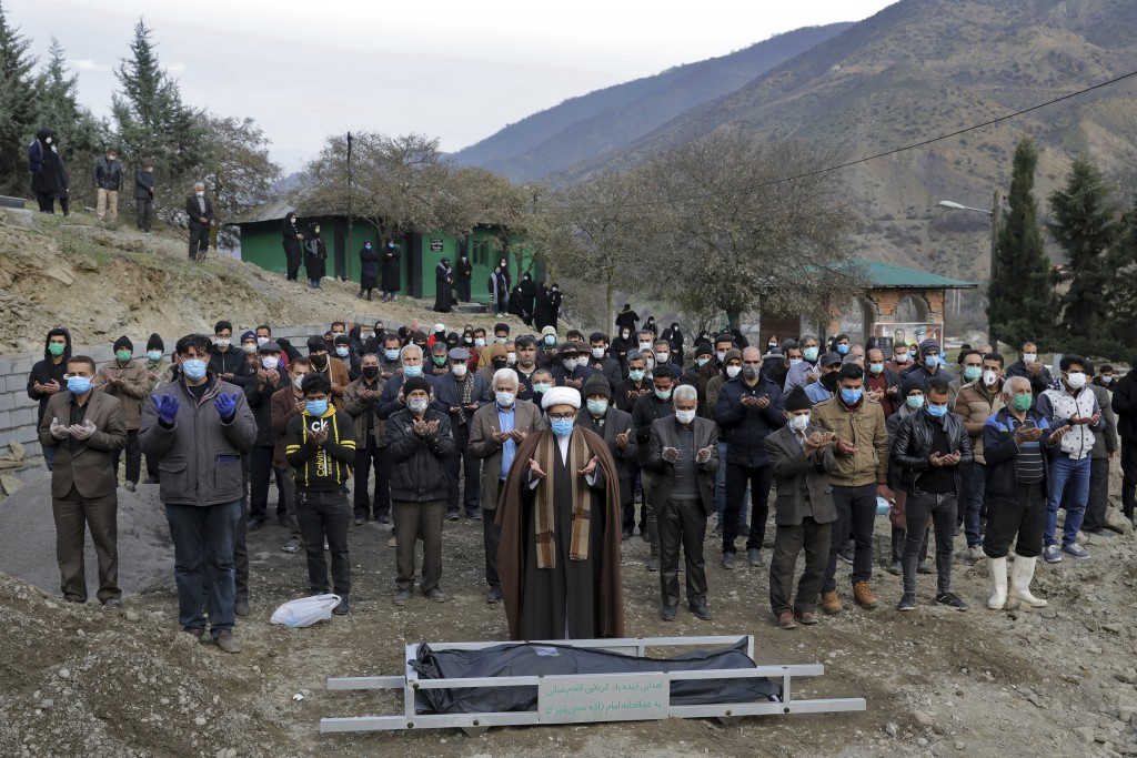 Mourners pray over the body of Keyumars Ziaee, 60, who died from COVID-19 at a cemetery in the Shir Kola village on the outskirts of the city of Ghaem...