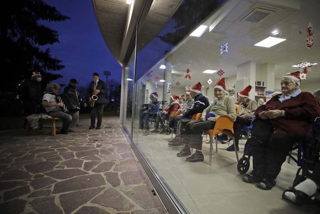 FILE - In this Dec. 19, 2020, file photo, hosts, protected by glass window, attend a Christmas concert in a nursing home in Alzano Lombardo, one of th...