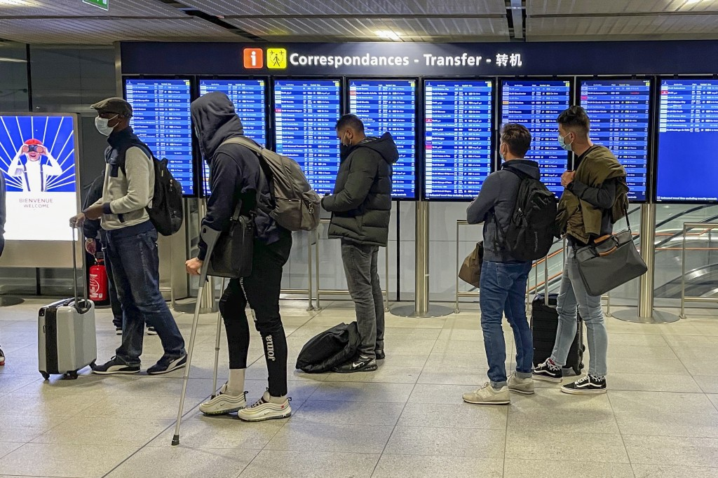 Transit passengers wait in line upon their arrival at Paris Charles de Gaulle airport Tuesday Dec. 22, 2020. More and more countries around the world ...
