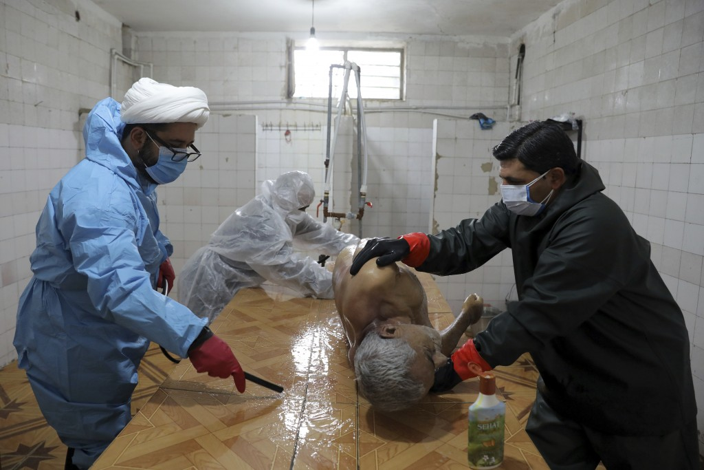Volunteers wearing protective clothing prepare the body of a 60-year-old man who died from COVID-19 for a funeral at a cemetery on the outskirts of th...