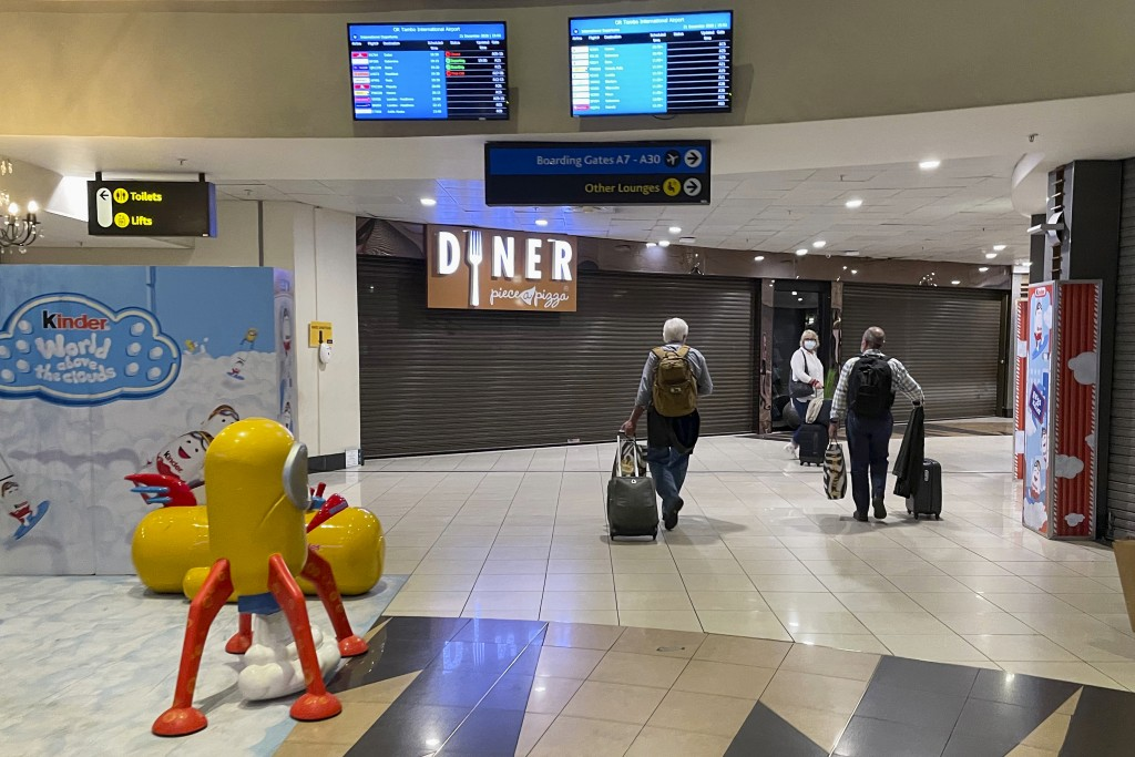 Passengers walks through the deserted air-side departure international terminal at Johannesburg's OR Tambo airport Monday Dec. 21 2020. More and more ...