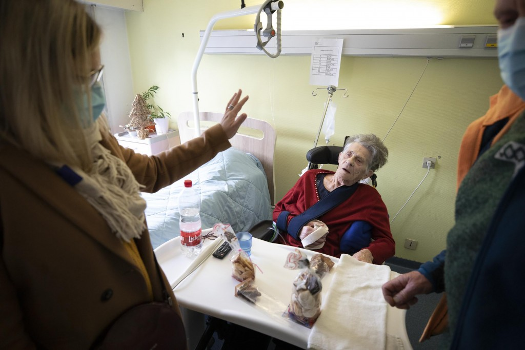Angele Martin gets Christmas cookies from her family at a nursing home in Kaysesberg, eastern France, Monday Dec. 21, 2020. France is springing elderl...