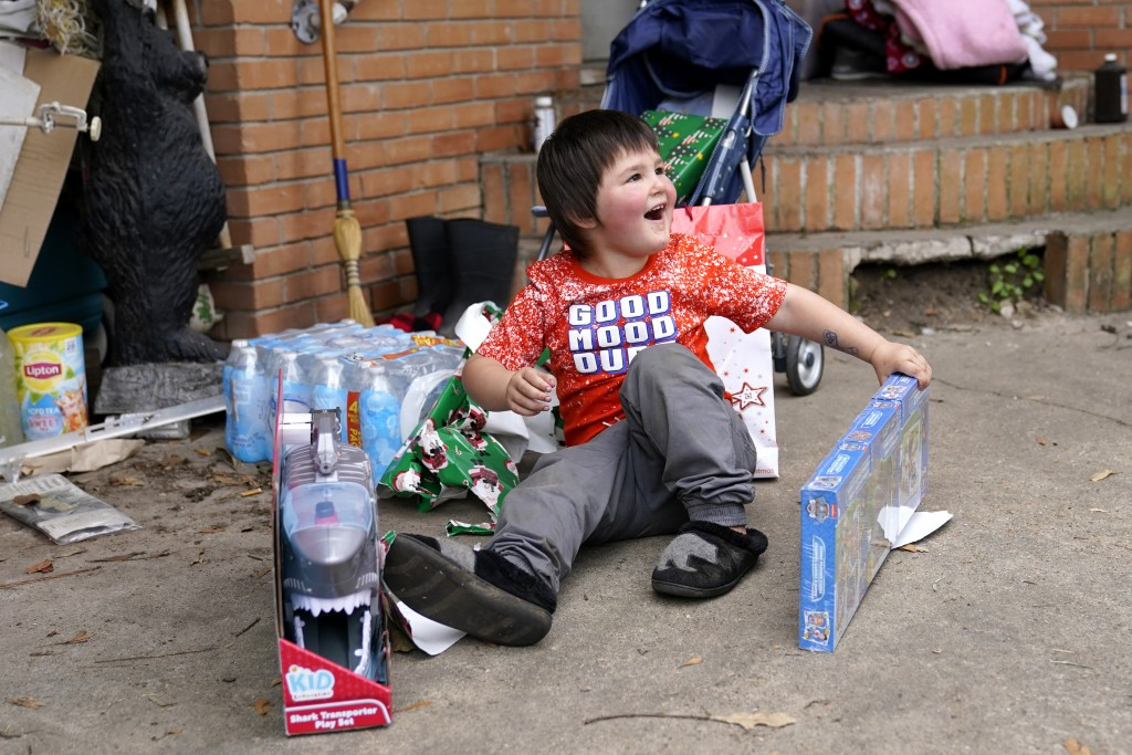 Conner Bourque reacts as he opens Christmas presents brought by church volunteers, where he lives with his family in a camper outside their heavily da...