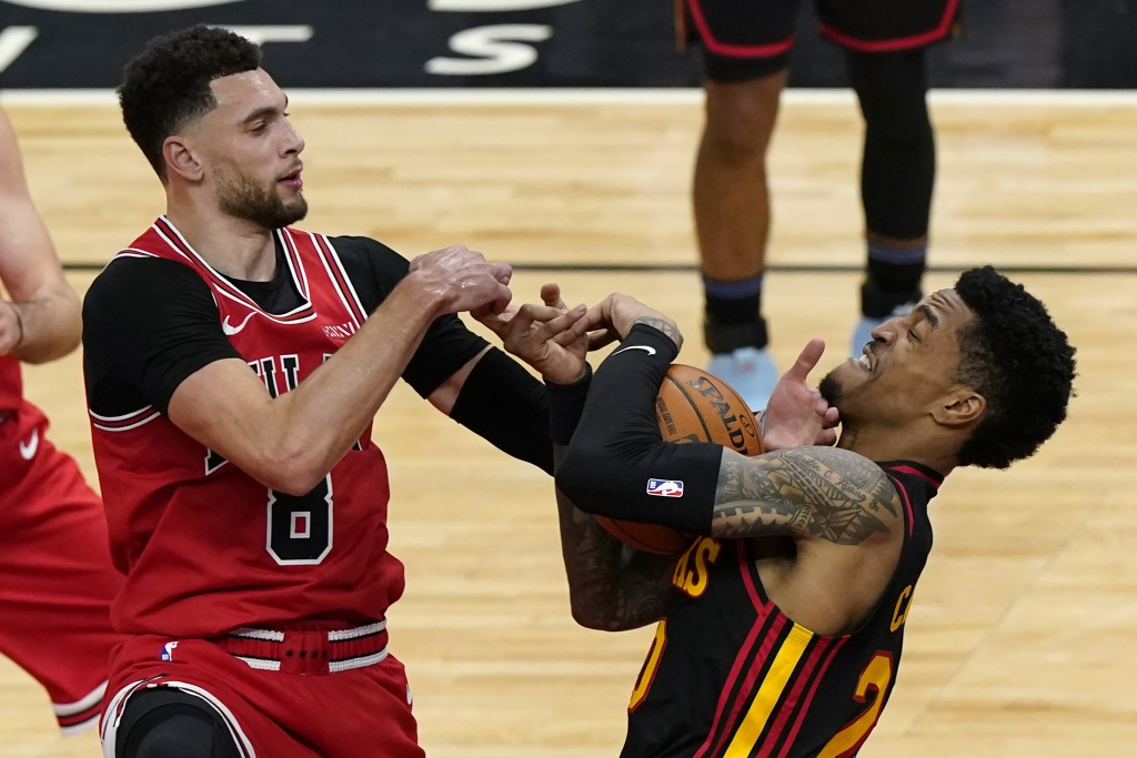 Atlanta Hawks' John Collins, right, battles for a rebound against Chicago Bulls' Zach Lavine during the first half of an NBA basketball game in Chicag...