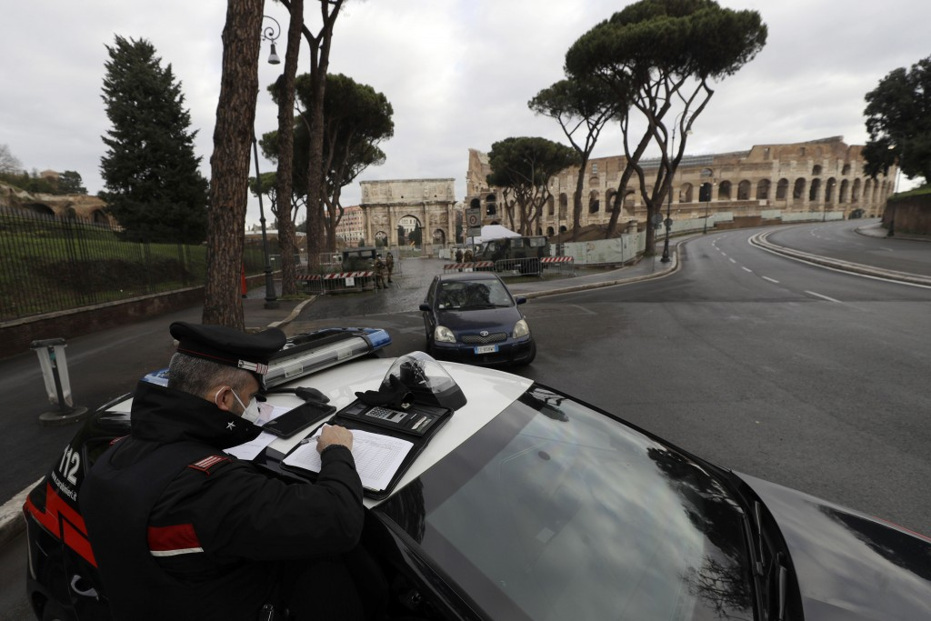 Italian Carabinieri officers check vehicles near the Colosseum in Rome, Thursday, Dec. 24, 2020. Italians are easing into a holiday season full of res...