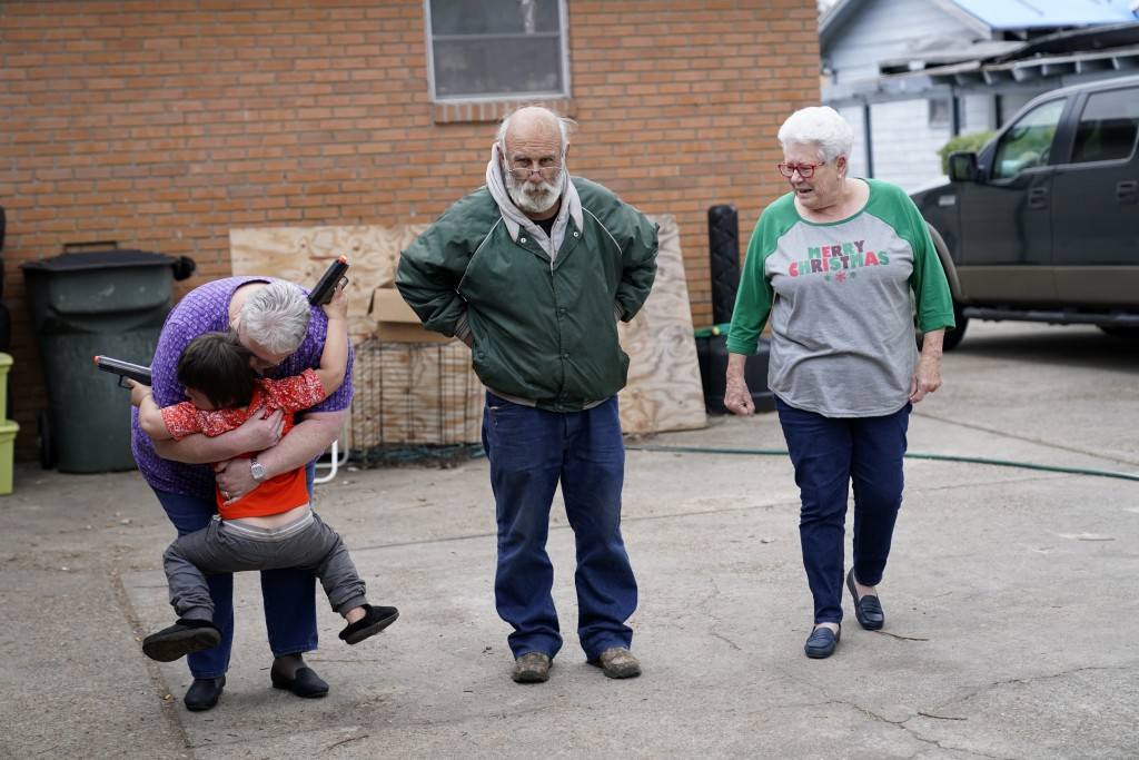 Janice Morgan, a church volunteer, hugs Conner Bourque as she arrives with Brenda Lee to bring him Christmas presents, in the aftermath of Hurricane L...