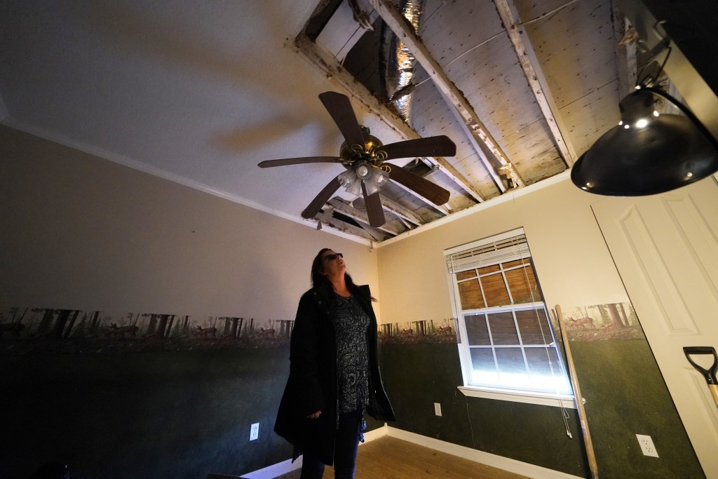 A warped ceiling fan hangs near a hole in the roof of Dewana Young's heavily damaged home, in the aftermath of both Hurricane Laura and Hurricane Delt...