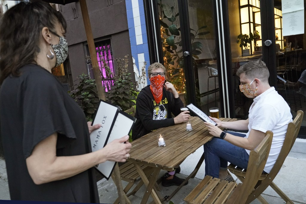 FILE — In this Sept. 29, 2020 file photo, restaurant owner Samantha DiStefano, left, of Mama Fox, prepares to hand menus to patrons dining outside at ...