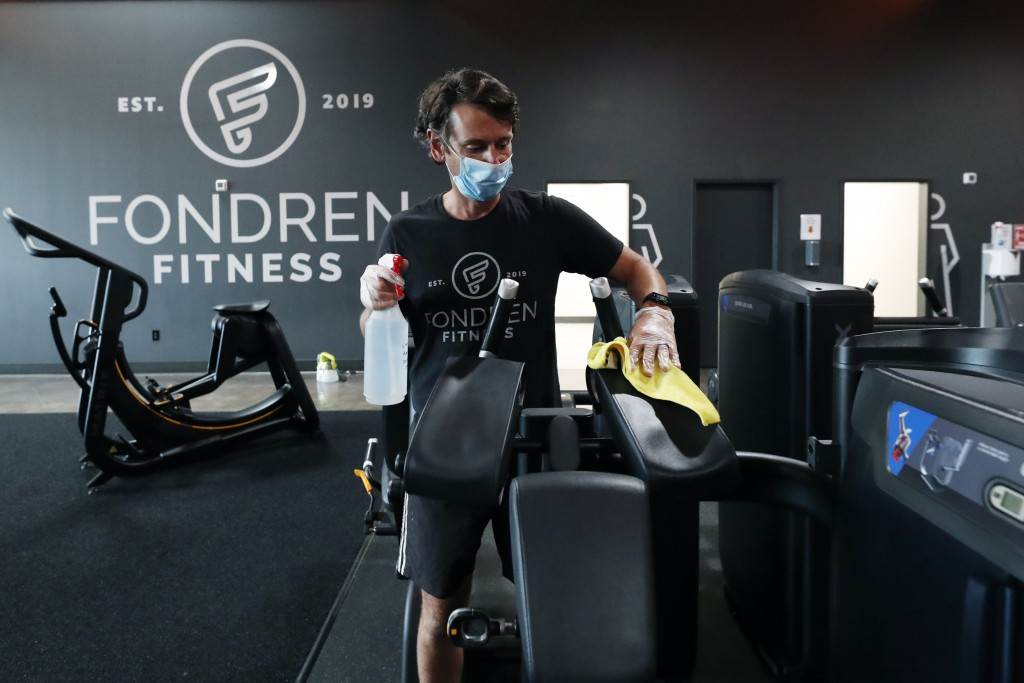 FILE - In this May 14, 2020 file photo, Terry Sullivan, general manager of Fondren Fitness, a Jackson, Miss., fitness center, sanitizes a workout mach...