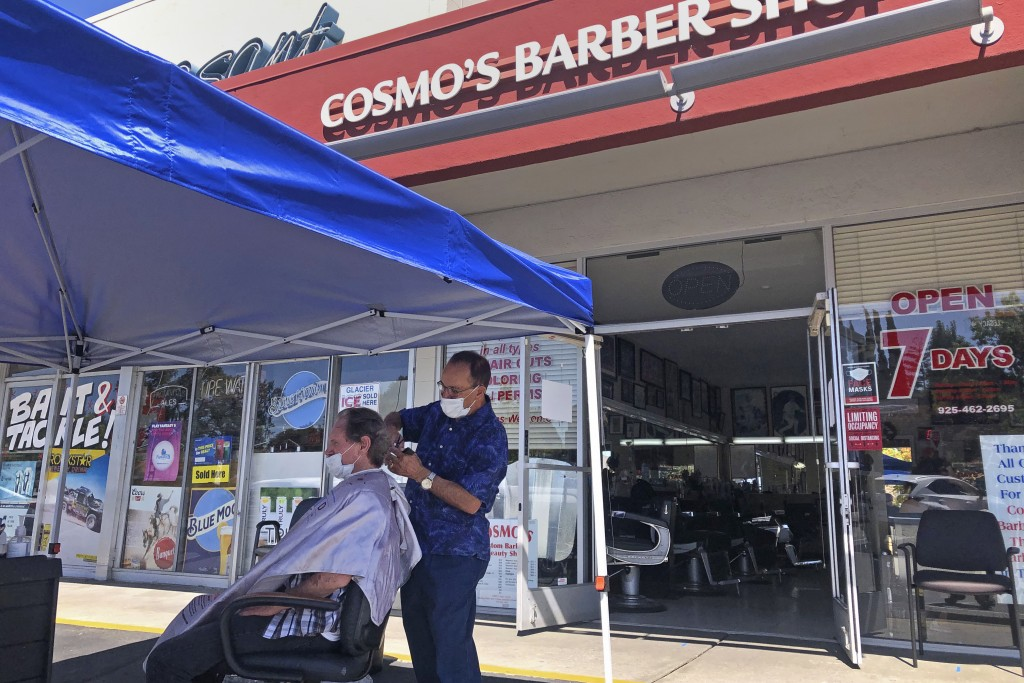 FILE - In this July 22, 2020 file photo, a customer of Cosmo's barber shop receives a haircut in the parking lot in front of the shop  in Pleasanton, ...