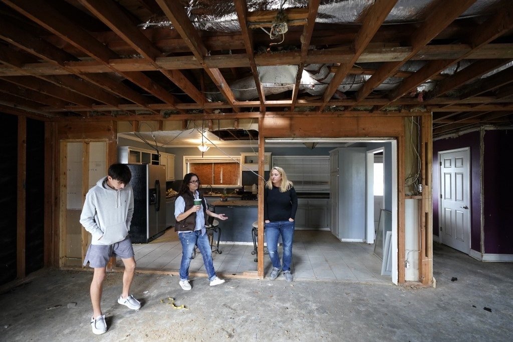 Christi, center, and Brandy Monticello, walk through their heavily damaged and gutted home, with their son Brennan Ash, in the aftermath of Hurricane ...