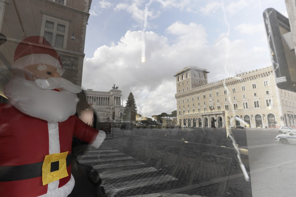 Empty Piazza Venezia Square is reflected in a window of a closed shop in Rome, Thursday, Dec. 24, 2020. Italians are easing into a holiday season full...