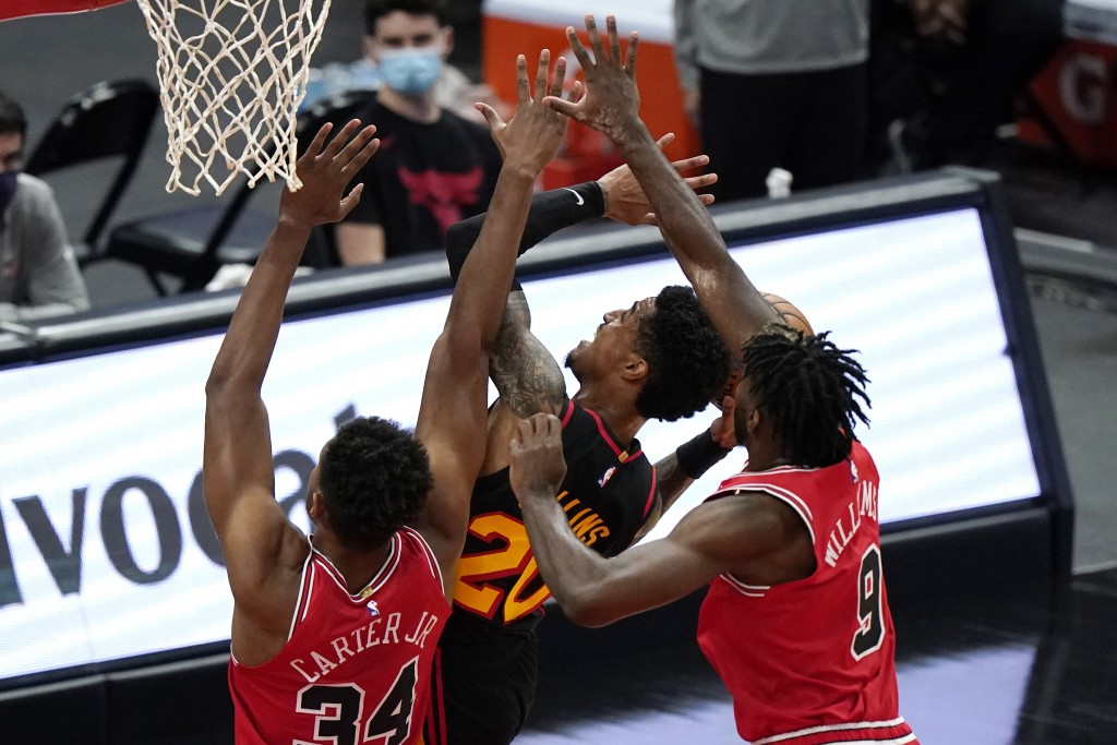 Atlanta Hawks' John Collins, center, drives to the basket between Chicago Bulls' Wendell Carter Jr., left, and Patrick Williams during the first half ...
