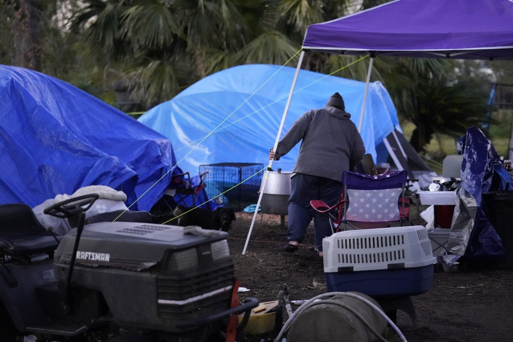 Sherry Bourque walks to the tent she is living in, in the back yard of her fathers heavily damaged home, in the aftermath of both Hurricane Laura and ...