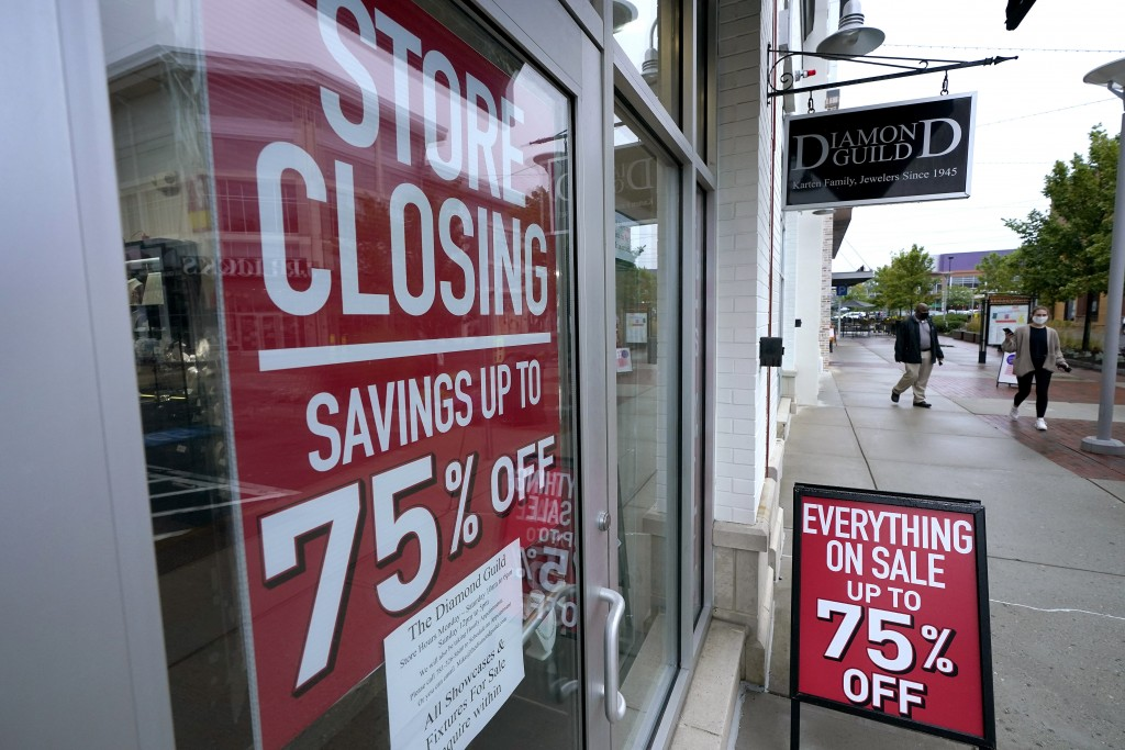 In this Sept. 2, 2020 photo, aassers-by walk past a business storefront with store closing and sale signs in Dedham, Mass.  The coronavirus and the dr...