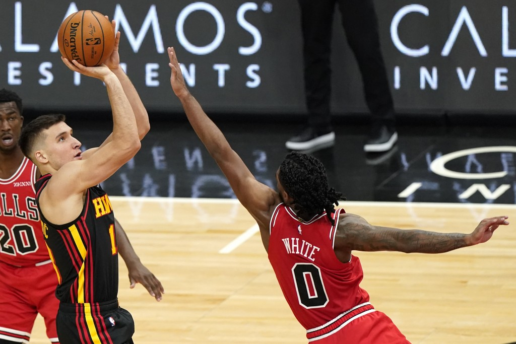 Atlanta Hawks guard Bogdan Bogdanovic shoots as Chicago Bulls guard Coby White, right, defends during the second half of an NBA basketball game in Chi...