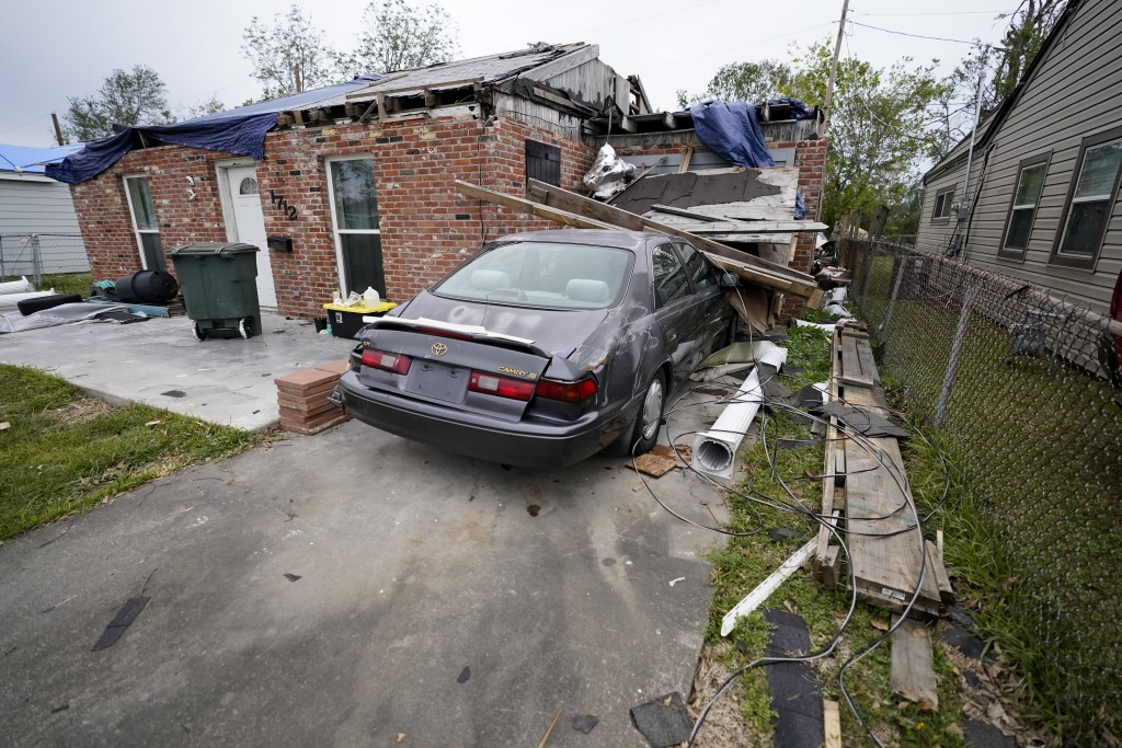 A heavily damaged home and car sit unrepaired in the aftermath of Hurricane Laura and Hurricane Delta, in Lake Charles, La., Friday, Dec. 4, 2020. (AP...