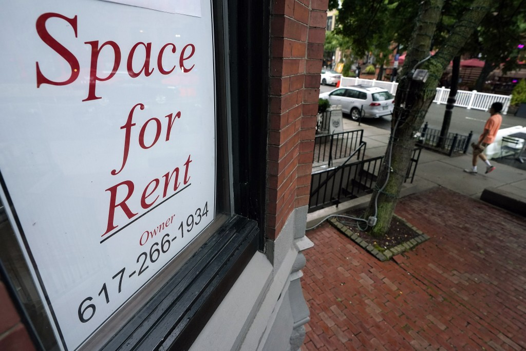 In this Sept. 2, 2020 photo, a passer-by walks past a business storefront with a space for rent sign in a window in Boston.  Commercial real estate ha...