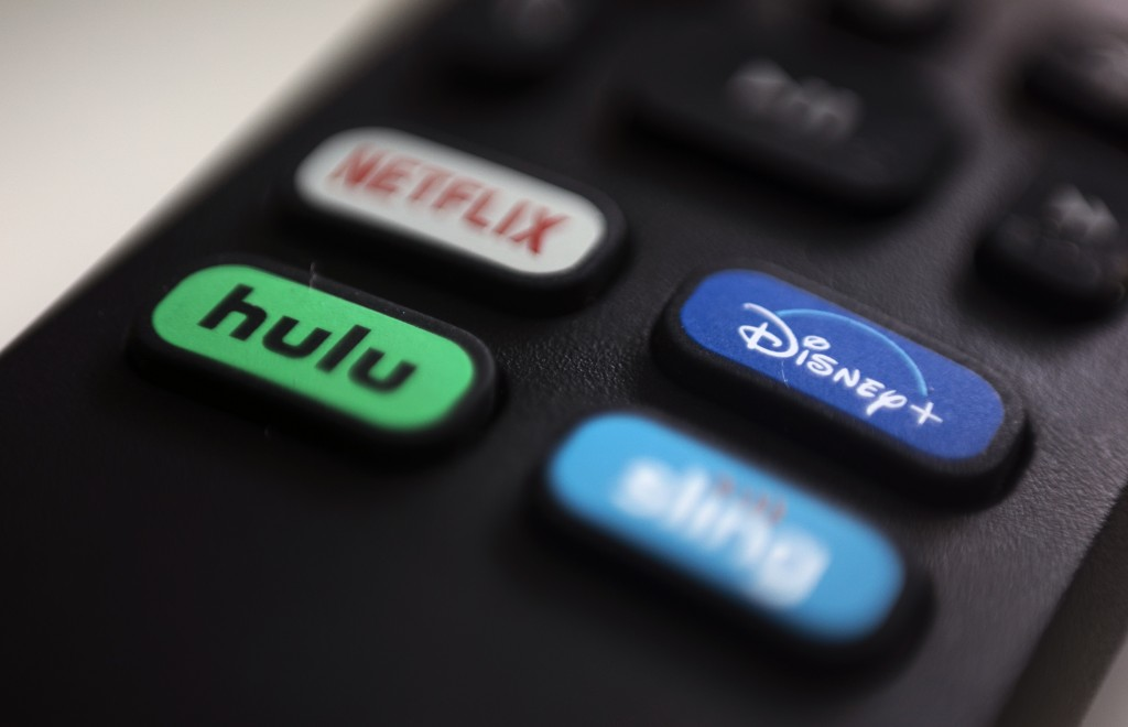 FILE - In this Aug. 13, 2020 file photo, the logos for Netflix, Hulu, Disney Plus and Sling TV are pictured on a remote control in Portland, Ore.  As ...