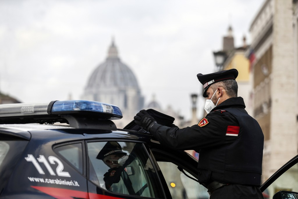 Italian Carabinieri officers check vehicles in front of St. Peter's Basilica, whose dome is visible in background, at the Vatican, Thursday, Dec. 24, ...